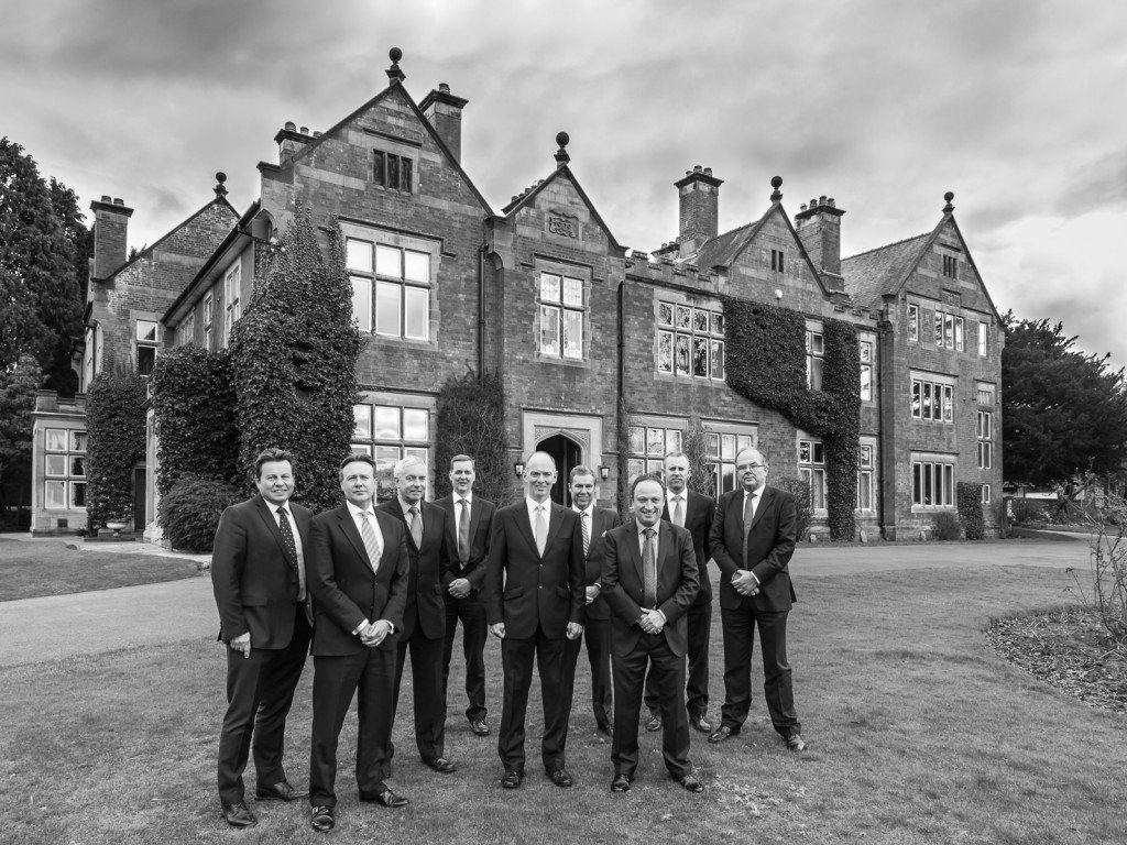 A group of businessmen standing outside a large country house