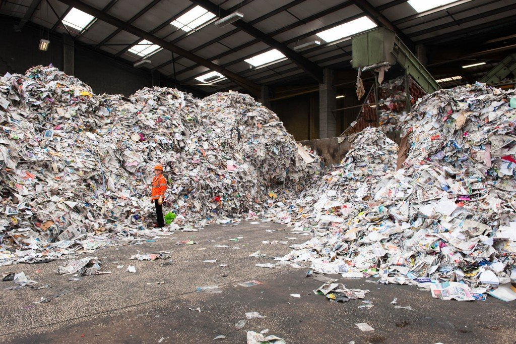 A woman in high vis jacket stands next to a pile of waste paper
