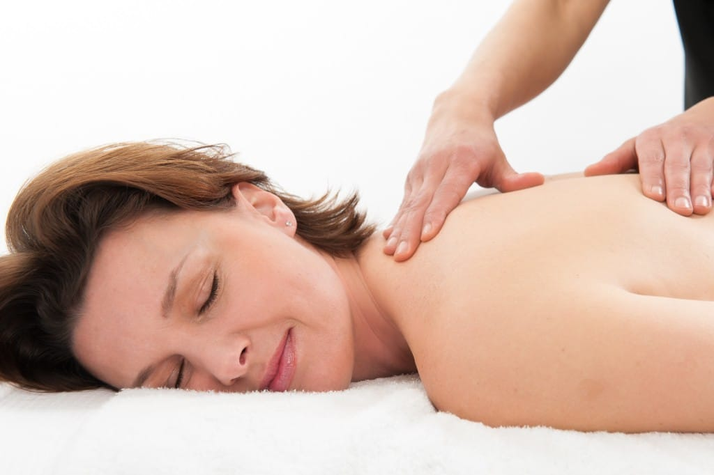 A woman lying down whilst receiving massage