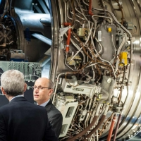 Businessmen in discussion in front of an aero engine at Rolls Royce, Derby